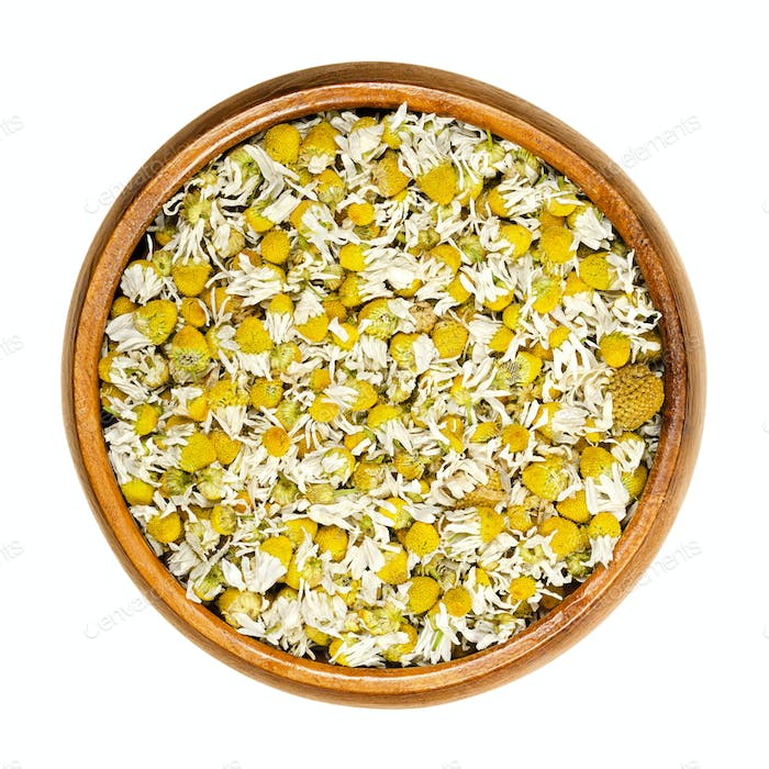 Dried chamomile blossoms, camomile tea in wooden bowl