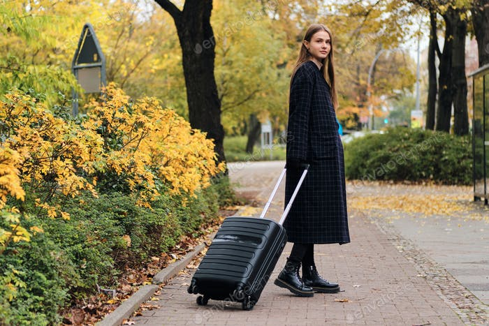 Beautiful stylish girl in coat with luggage bag intently looking in camera in park