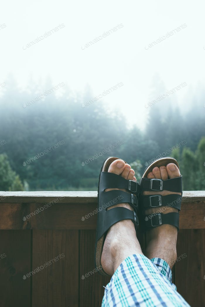 Man enjoying misty morning at mountain hotel balcony
