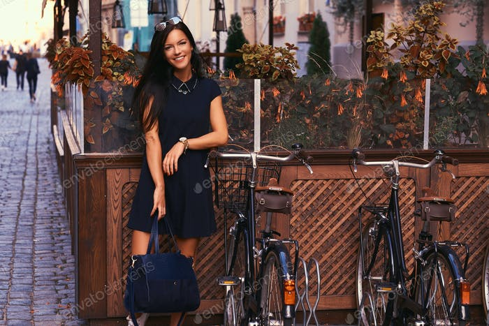 Brunette wearing stylish black dress posing near bicycles against a background of a cafe.