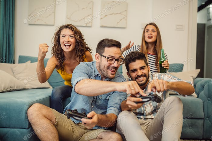 Friends having fun at home with video games.