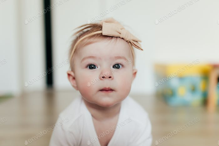 Little baby girl with bow looking at camera. Blurred background