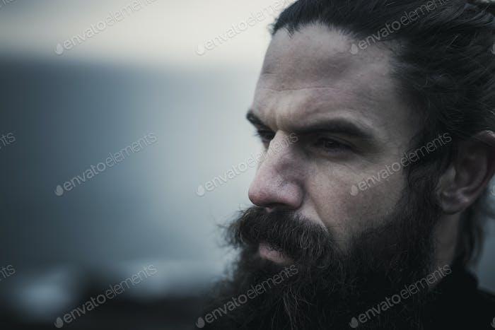 Человек с полной бородой и усами и черными волосами свернул с лица.