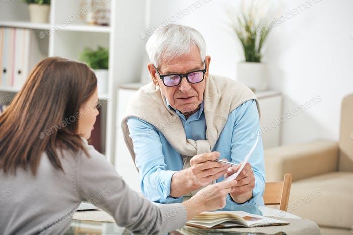 Young social worker or insurance agent asking questions of senior man