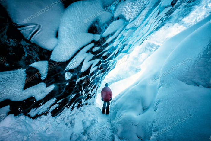 Hiker walking in ice cave