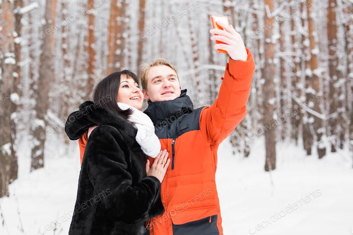 Couple taking self portrait with smart phone in winter park. Beautiful young couple selfie