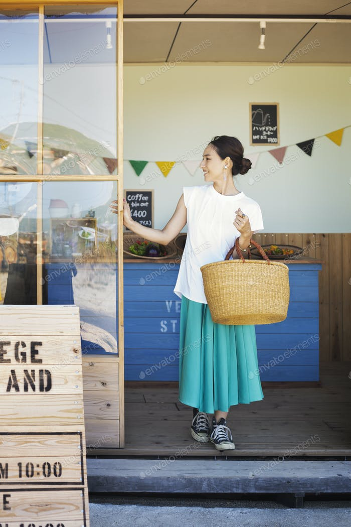Japanese woman standing outside a farm shop, holding shopping bag.