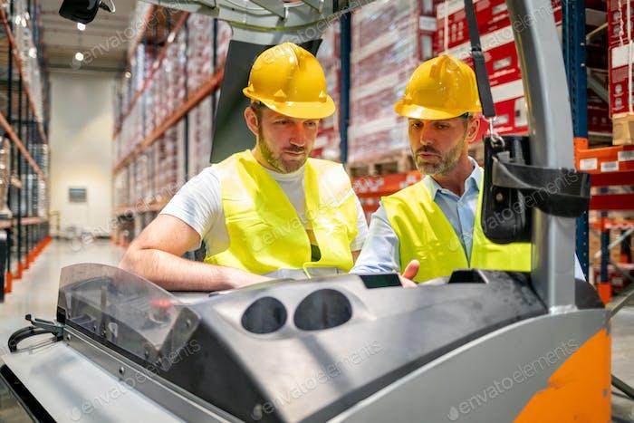 Lagerarbeiter lernt mit Instruktor, wie man Gabelstapler benutzt