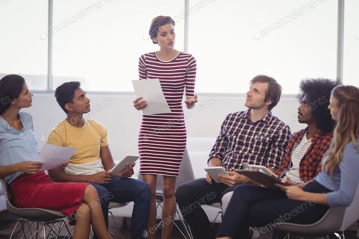 Colleagues listening to businesswoman in creative office