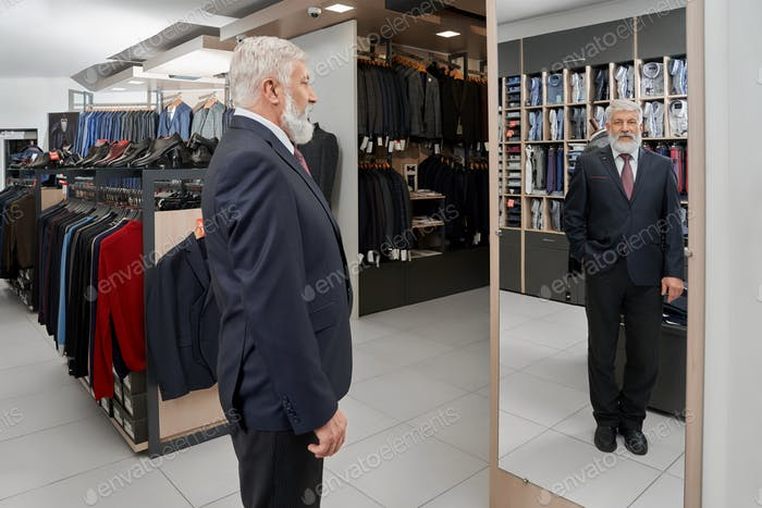 Elder man official smart suit looking at mirror in boutique
