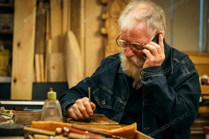 Senior wood carving professional with mobile phone