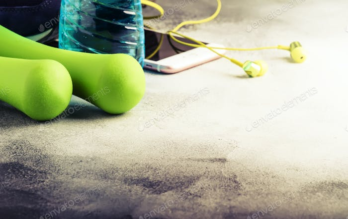 Female fitness concept: light green dumbbells, isotonic blue water, smartphone