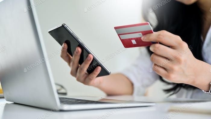 Junge Frau hält Kreditkarte und Smartphone mit Laptop, Kreditkartenzahlung.