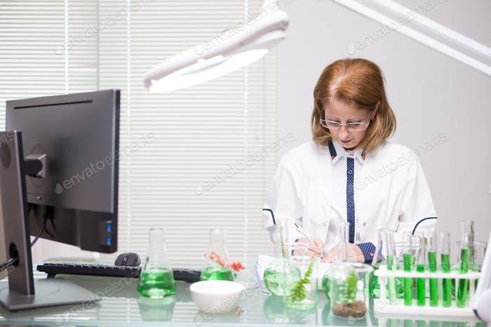 Focused middle age woman taking notes after scientific test in a production laboratory