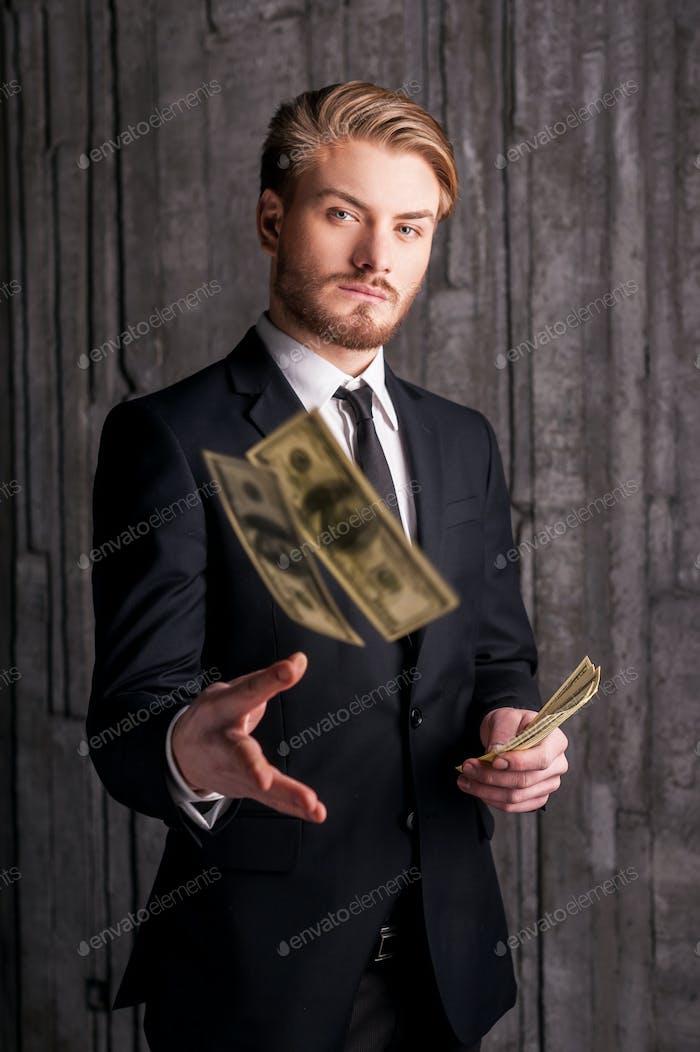Reich und erfolgreich. Schöner junger Mann in Formalwear, der Geld wirft und in die Kamera blickt