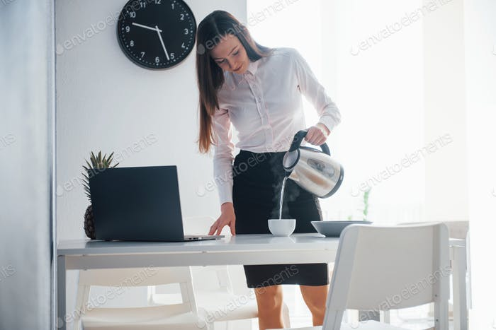 Fresh tea. Young businesswoman with black hair in official clothes at her home