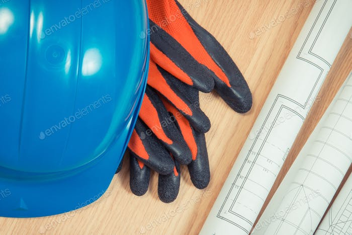 Rolls of electrical blueprints, protective blue helmet and gloves