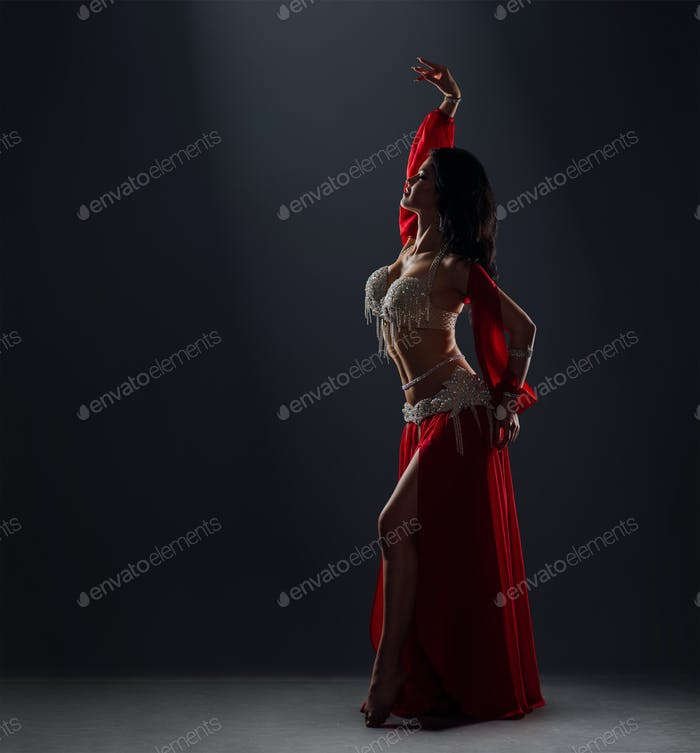 beautiful black-haired girl in red ethnic dress dancing oriental belly dance on stage in the dark