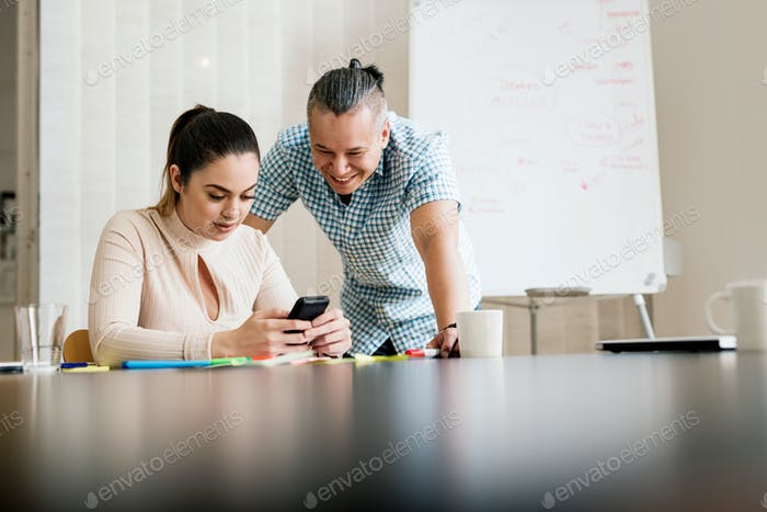 Coworkers looking at mobile phone in board room