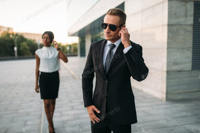Bodyguard in sunglasses and black business woman