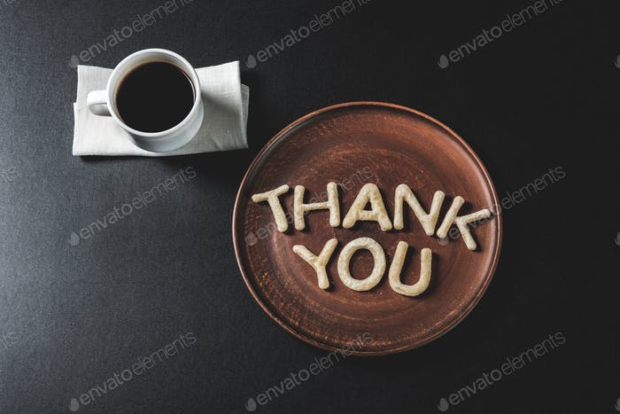 top view of lettering thank you made from cookie dough on wooden plate with coffee cup