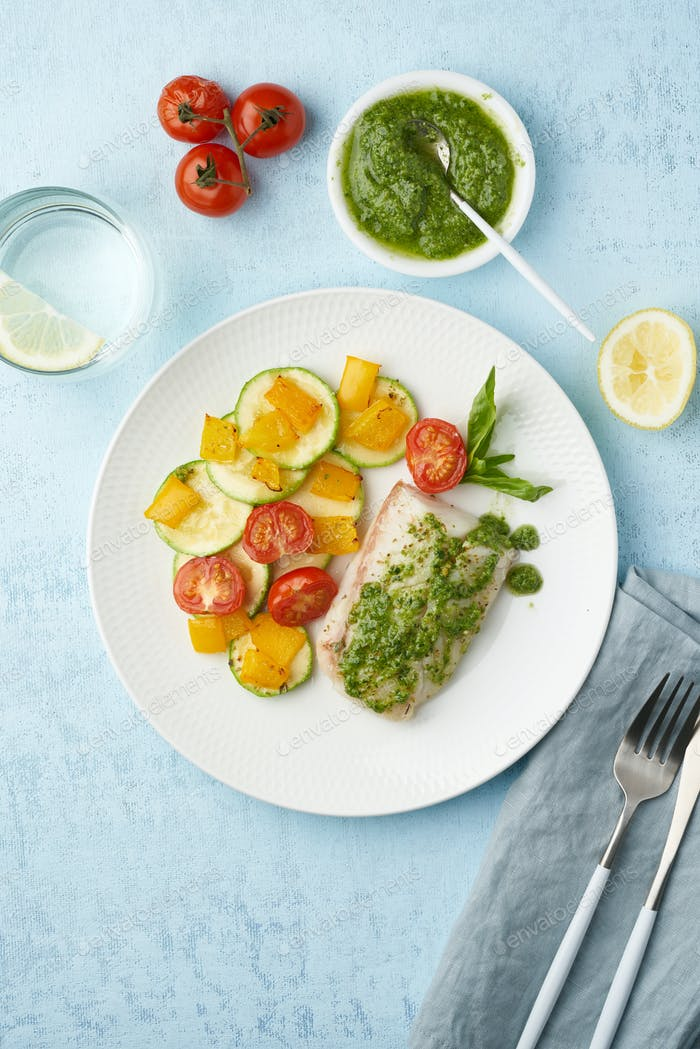 Keto dinner with white fish. Oven baked fillet of cod, pike perch with vegetables and pesto sauce