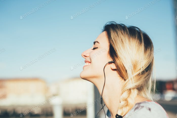 Profile portrait of young beautiful caucasian woman listening mu