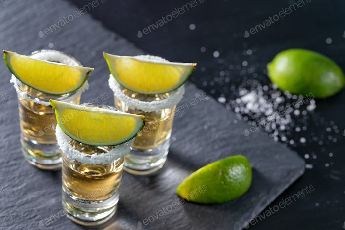 Three glasses of mexican tequila and lime on dark background