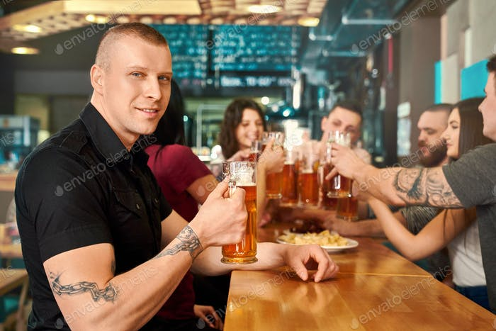 Side view of tattooed man keeping glass of beer in pub