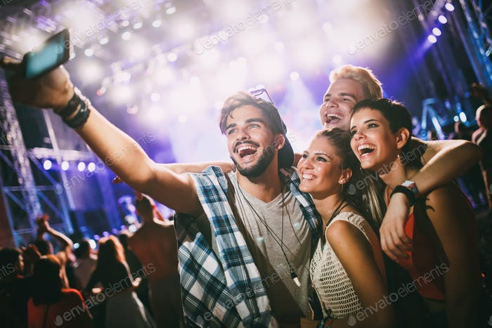 Happy friends taking selfie at music festival