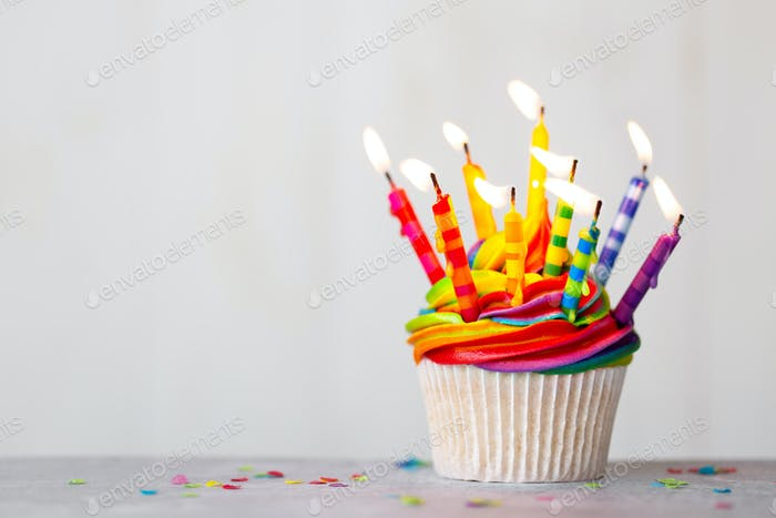 Birthday cupcake with rainbow frosting and candles