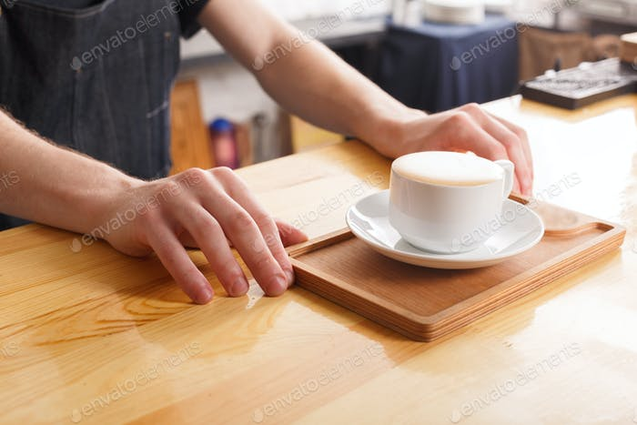Barman serving coffee cup on wooden bar counter