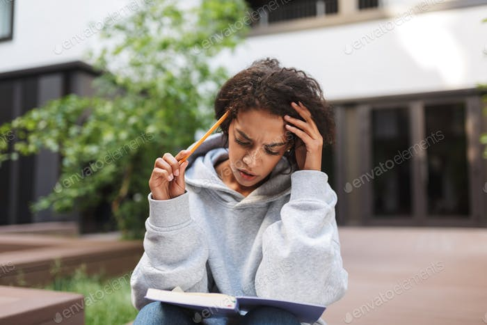 Thoughtful lady with dark curly hair sitting with notebook on knees and pencil in hand