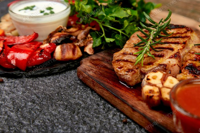 Steak pork grill on wooden cutting board with a variety of grilled vegetables.