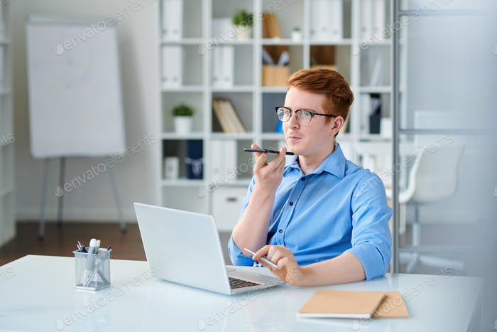 Young elegant businessman recording voice message by workplace