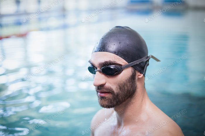 Focused man wearing swim cap and goggles at the pool