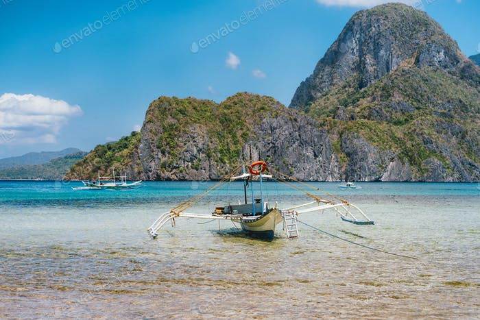 Palawan, Philippines. Traditional filippino banca boat in shallow blue tropical lagoon in El Nido