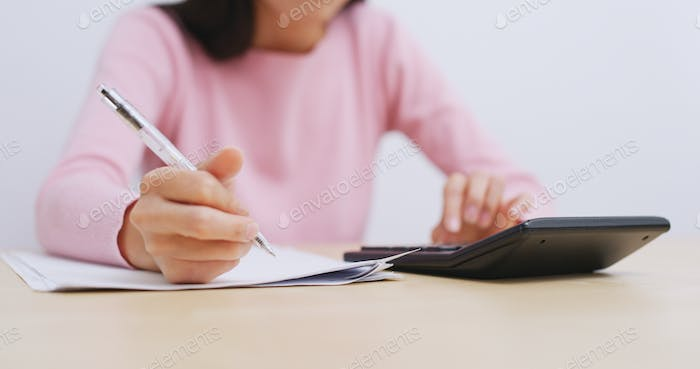 Woman using calculator and writing on paper