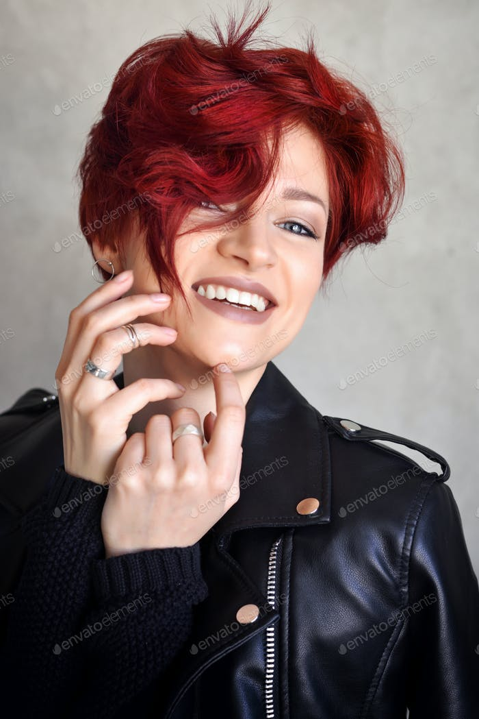 Portrait of emotive red-haired young woman laughing
