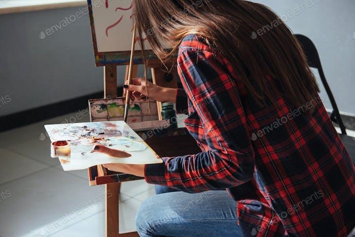 Pretty Pretty Girl artista pinta sobre lienzo en el caballete.