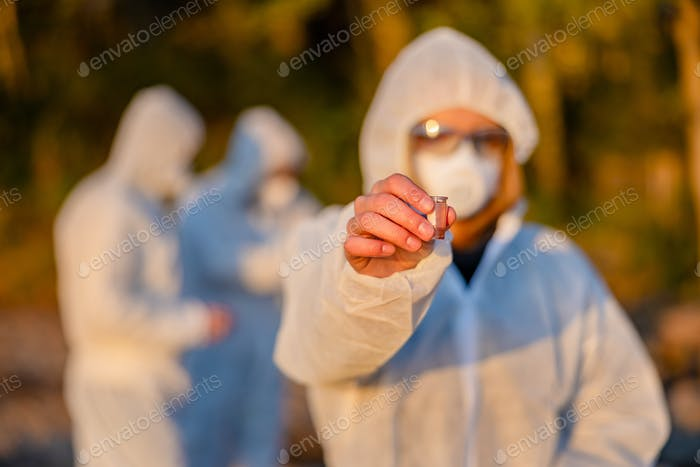 Scientist in white protective suit holding water sample at beach