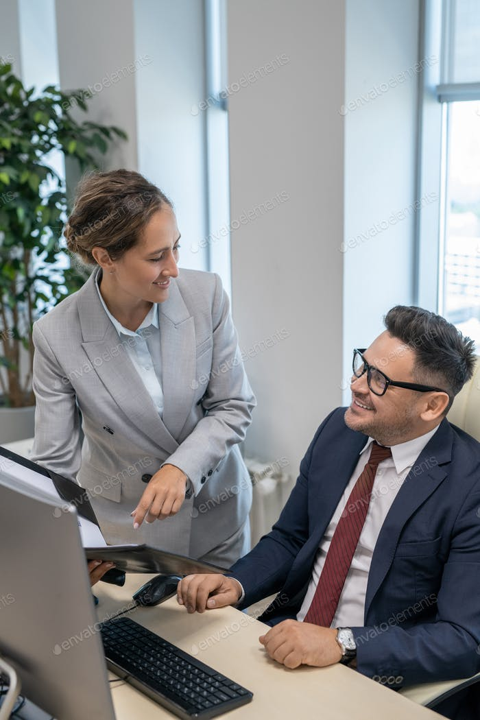 Elegant secretary consulting with her boss in office