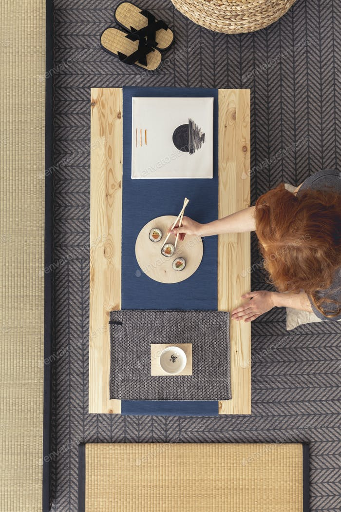 Top view of a ginger woman eating sushi at a wooden table with a