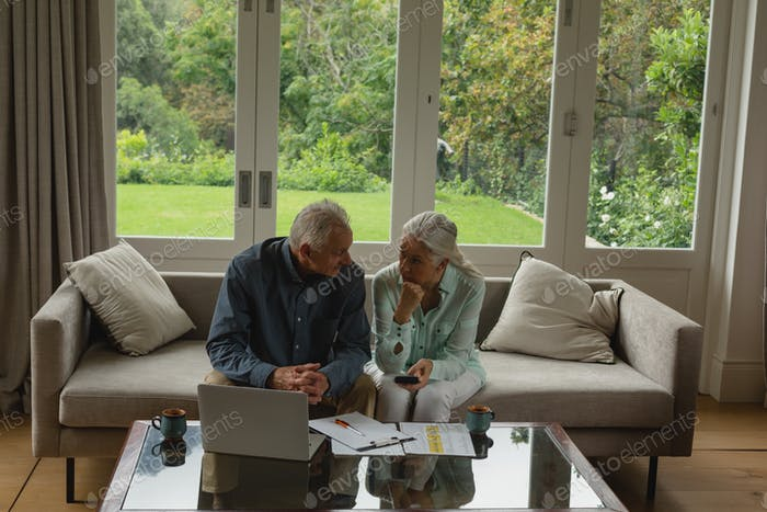 High view of active senior Caucasian couple calculating bills in living room at home
