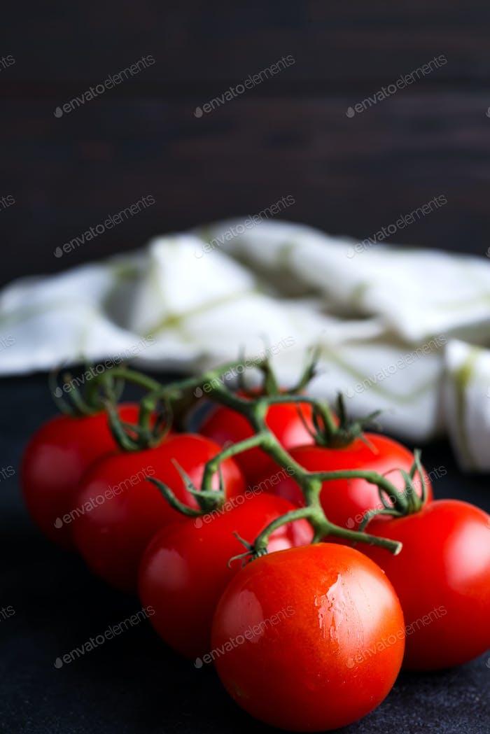 Frische reife Bio Tomatenzweig auf dunklem Hintergrund mit Textiltuch