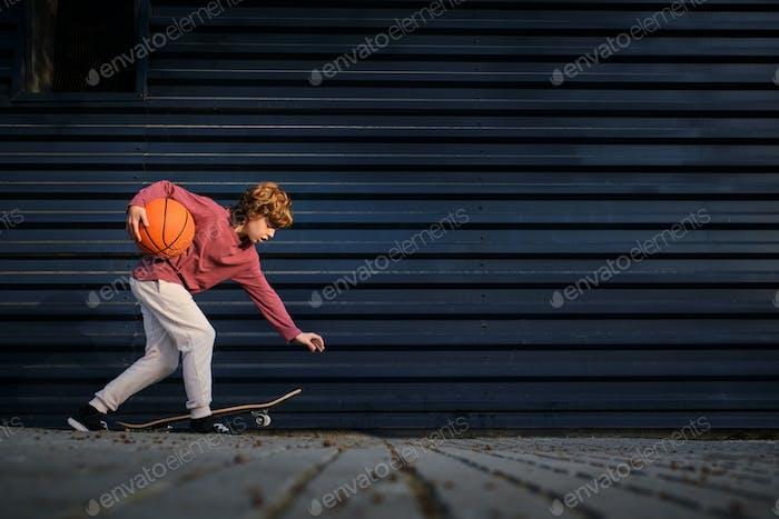 Boy and basketball ball on street