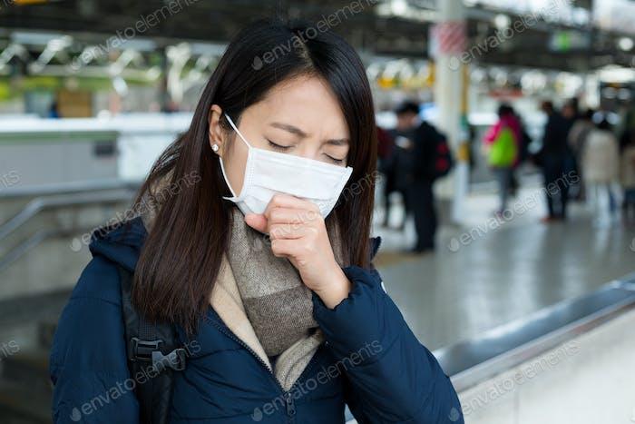 Frau fühlt sich unwohl und trägt Gesichtsmaske im Bahnhof
