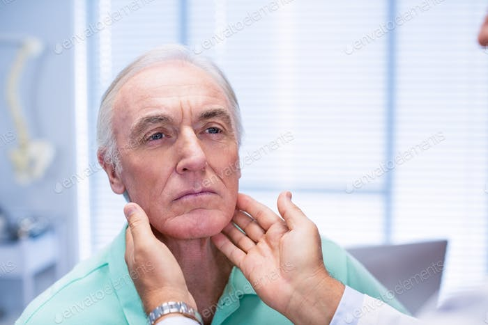 Doctor examining senior patients neck