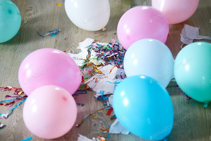The mess after the birthday celebration with balloons and confetti on the floor