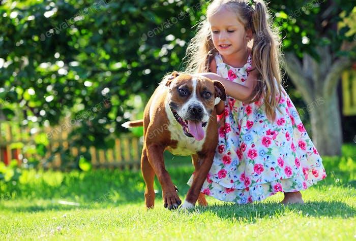 Niedlich kleines Mädchen spielen mit Ihr Staffordshire Terrier Hund